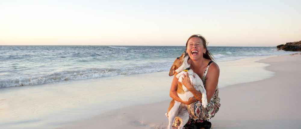 woman laughing with her dog on a beach
